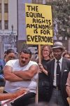 Woman_holding_Equal_Rights_Amendment_sign_in_Los_Angeles,_California,_with_two_men,_one_of_them_yawning